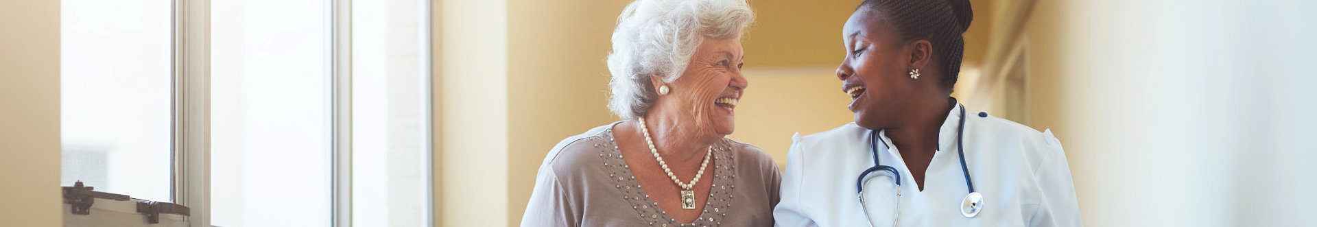 nurse and elder woman smiling to each other