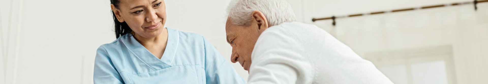 caregiver assisting the elder man to stand